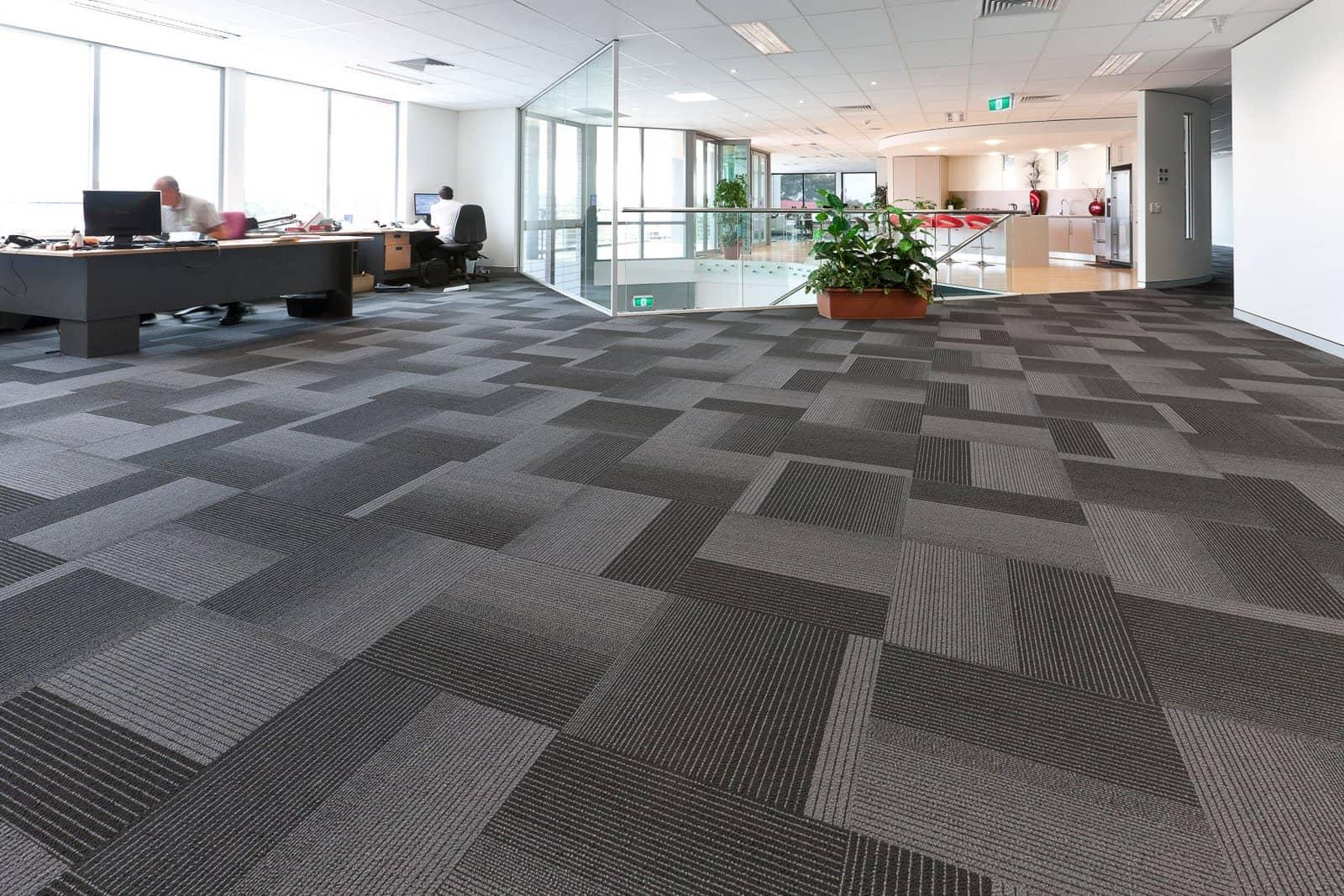 Kontor med store teppefliser i lyst grå og mørt grå